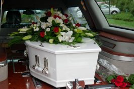 white coffin with flowers on