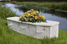 wicker coffin with funeral flowers