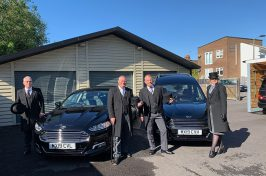 funeral directors in front of funeral cars